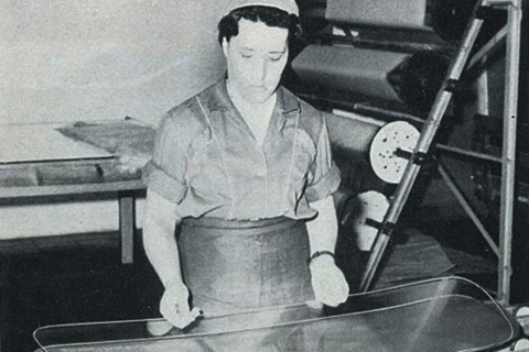 A worker manually merges the two glass panes with an interlayer.